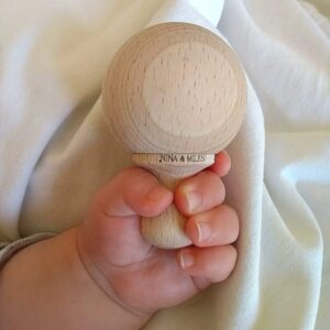mini maracas en bois tenue par la main d'un bebe