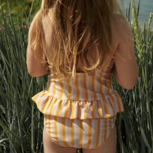 petite fille qui porte un maillot de bain une pièce jaune liewood