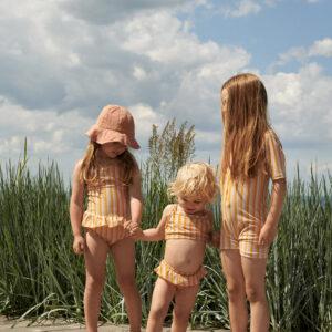 petites filles qui portent un maillot de bain une pièce jaune liewood