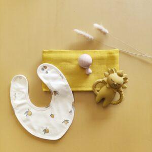 coffret naissance avec bavoir, anneau de dentition en silicone, mini maracas en bois et un lange moutarde en coton bio