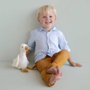 petit garçon assis qui sourit avec sa peluche oie