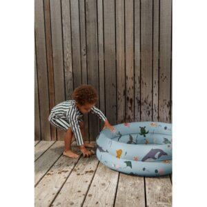 petite garçon qui joue avec sa piscine gonflable aux motifs animaux marins