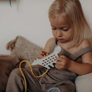 petite fille qui joue avec un jouet à lacer en forme de chien