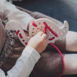 petite fille qui joue avec un jouet à lacer en bois en forme de dino