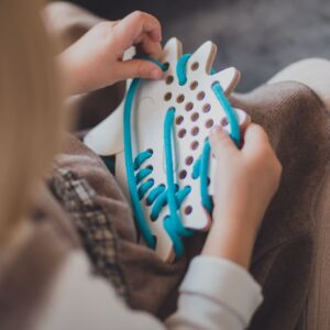 petite fille qui joue avec un jouet à lacer en bois en forme d'hérisson