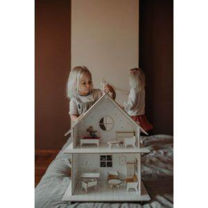petite fille qui joue avec sa maison de poupée en bois vintage et les souris maileg