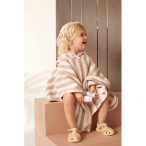 petite fille qui porte un poncho à capuche rayé rose creme de la marque liewood