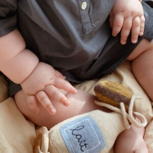 bébé qui joue avec son mobile musical en laine