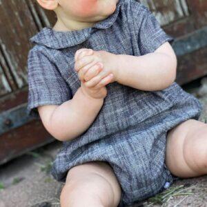 petite fille qui porte une barboteuse en gaze de coton gris chiné