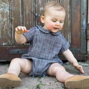 petite fille assise en extérieur portant une barboteuse en double gaze de coton gris chiné de la marque janne mill
