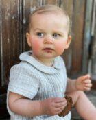 petite fille qui porte une barboteuse gris clair de la marque janne mill