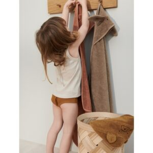 petite fille qui accroche sa cape de bain un porte manteau