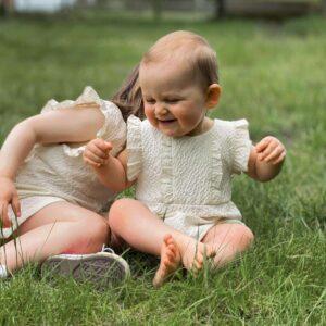 petites filles assises dehors qui portent une combishort creme janne mill
