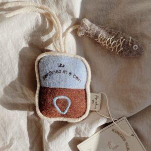 hochet d'activité en laine posé sur un lit